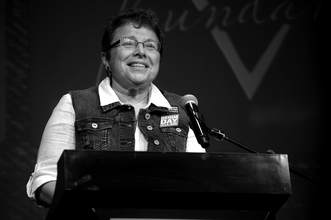 Denim Day Founder and Peace Over Violence Executive Director, Patti Giggans speaks on stage at the GUESS? Inc. Headquarters
