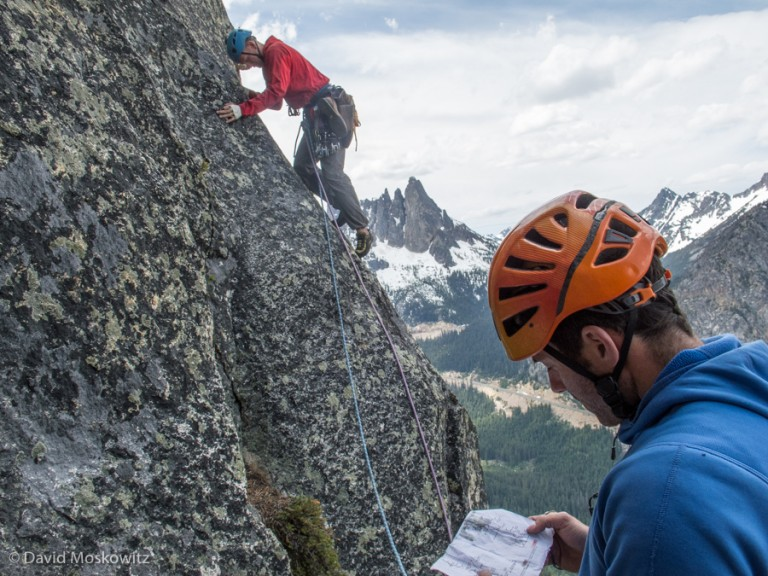 Josh Cole reviews the route description as Ryan sets off on another pitch of the route. Liberty Bell and the road cut of the North Cascades Scenic Highway can be seen in the distance.