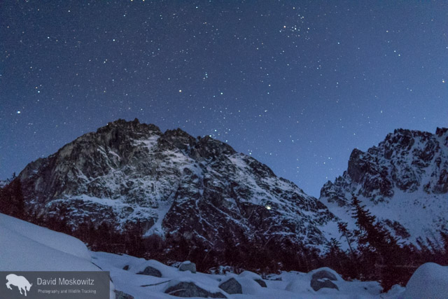 Dragon tail Peak in the moonlight. The Triple Couloirs route starts in the obvious snow gully around the center of the face. Note the headlamps on the right side of the face. From our camp on the lake we watched a party retreat off of the face via multiple rappels in the dark.