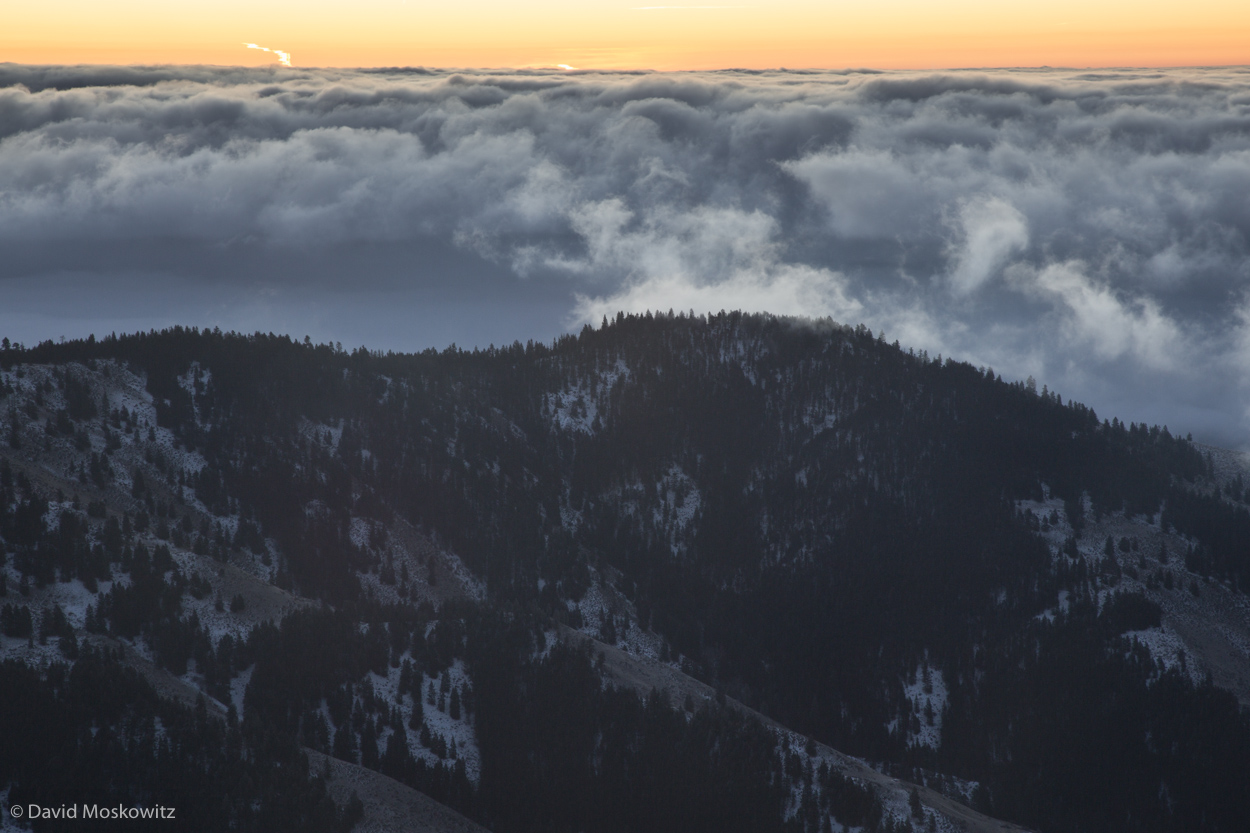 Low clouds sit over the valley at the first light of the day.