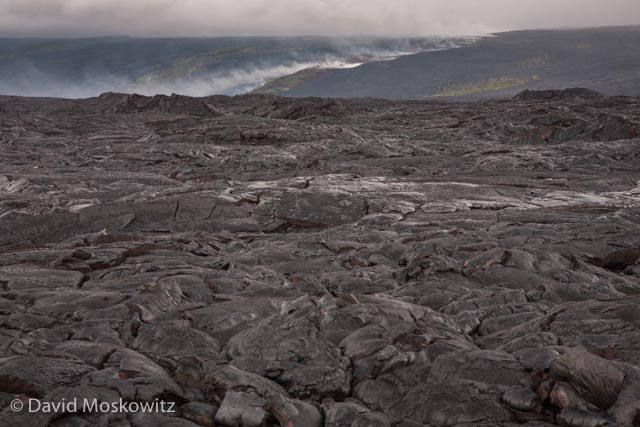 The line of smoke in the distance marks the path of lava flowing down from the rift where it comes out of the earth, seen here across a vast plane of basalt from the recent flows from this rift which has been releasing lava on and off for years.
