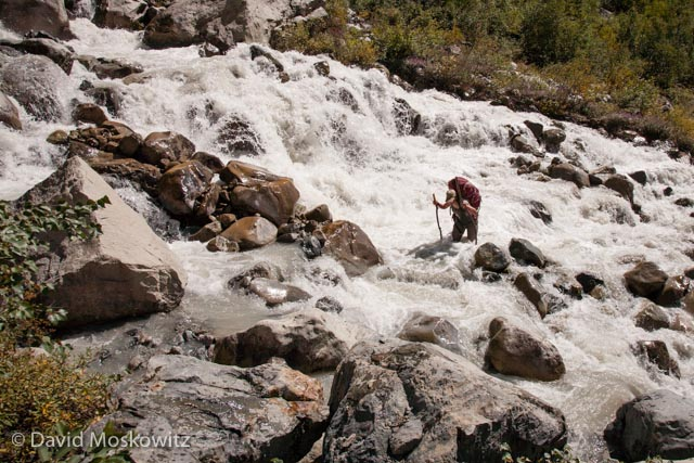 Intrepid traveler crossing the ragging glacial outflow several miles downstream from the snout of the Ushba glacier in the Republic of Georgia's Sveneti region.