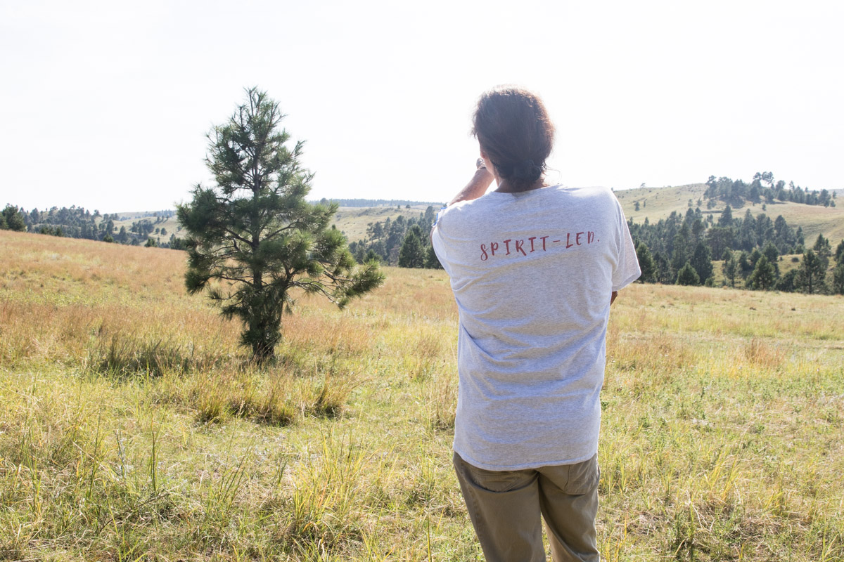 "Dallas Chief Eagle looks out across Pine Ridge. One of the driving principles behind All Nations Gathering Center, written across the back of his shirt, is ""Spirit Led."""