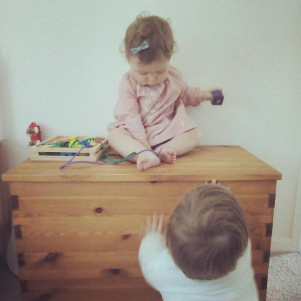 Cousins playing king of the castle on the Tinkebu Toybox.