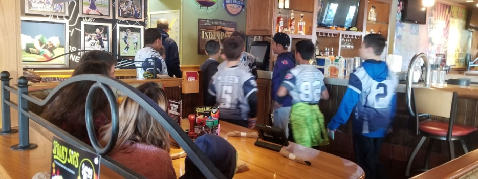 The football players take their places as waitstaff for the day.