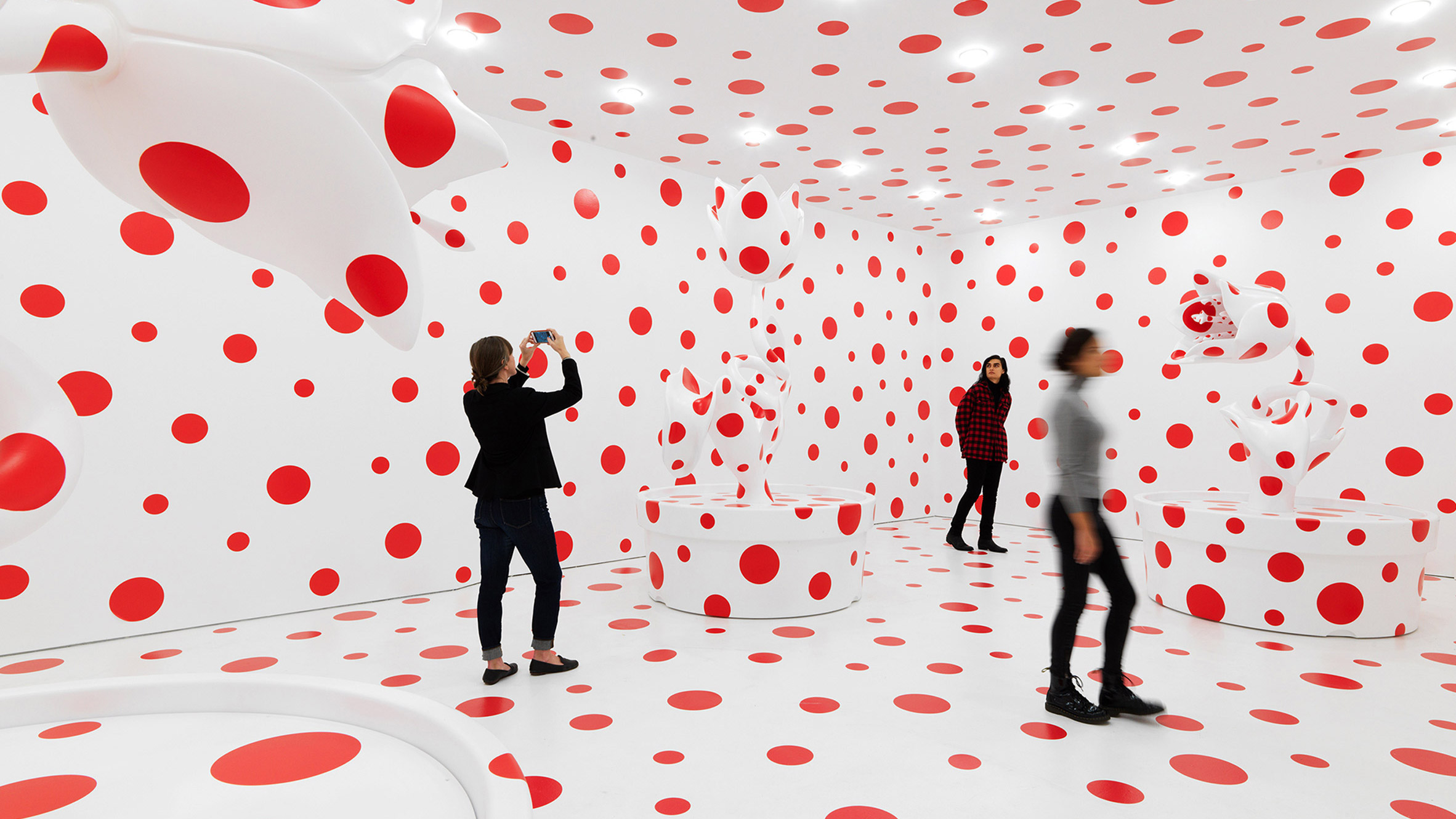 "Audience member's photographing Yayoi Kusama's polka dot installation, another example of a ""blockbuster."" Image from  Deneze"