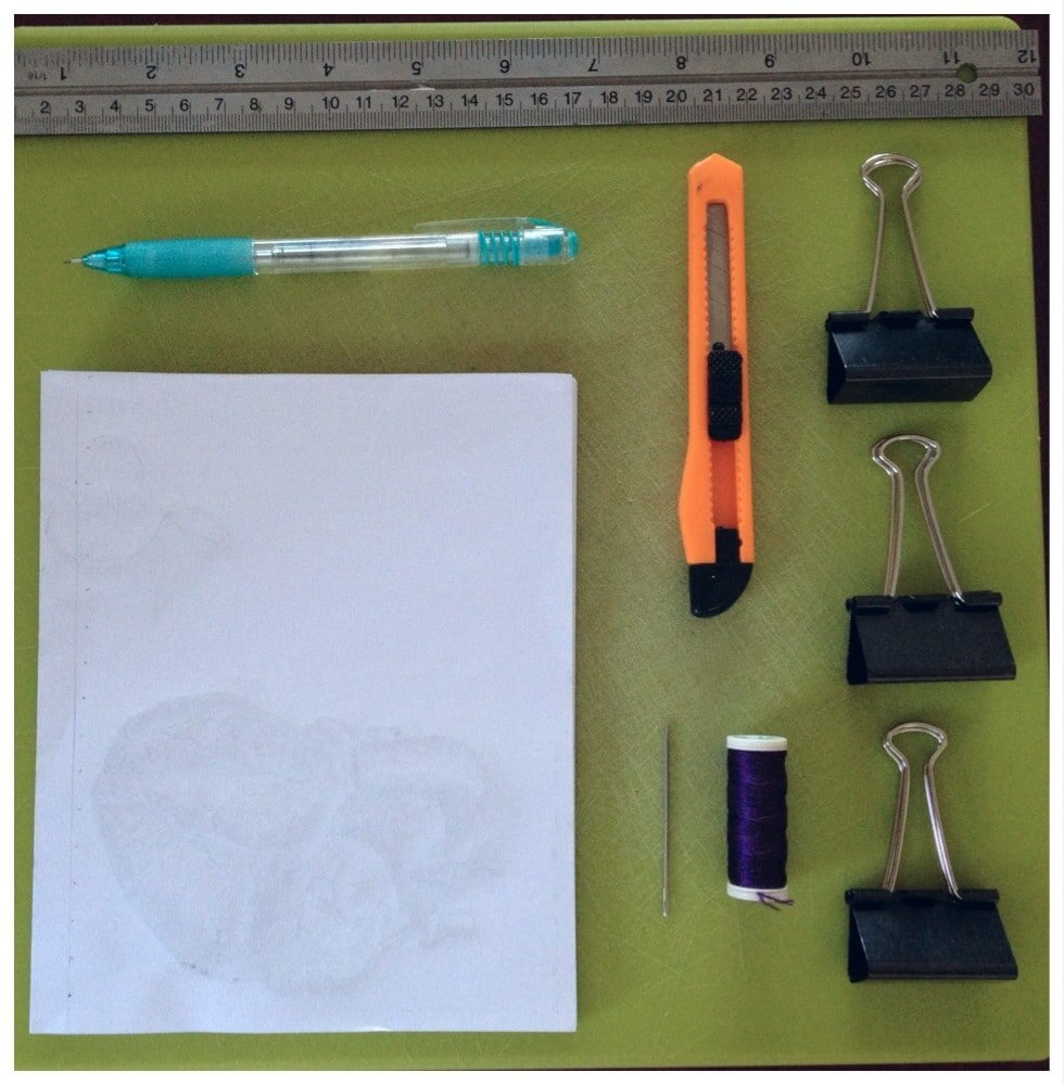 FROM TOP TO BOTTOM:    GREEN CHOPPING BOARD (AKA CUTTING BOARD), RULER, PENCIL, CRAFT KNIFE, 3 X BULLDOG CLIPS, USED PRINTER PAPER, DARNING NEEDLE, SILK THREAD FOR DECORATIVE STITCHING