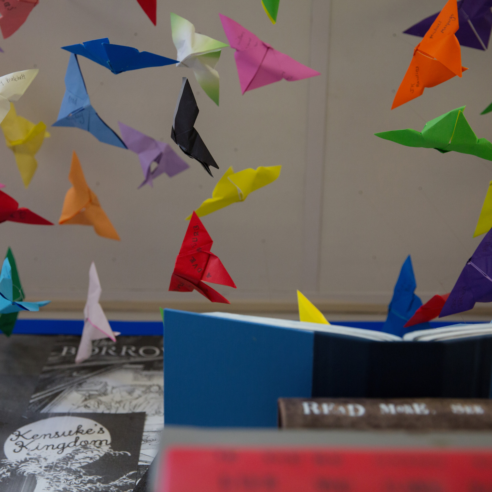 colourful origami butterflies bursting out of art book display