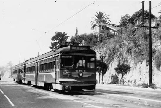 Starting in 1894, Moses Sherman and Eli Clark began acquiring the various cities' horse-car and cablecar systems, eventually forming the Los Angeles Consolidated Electric Railway. In 1895 the first intercity line opened; an electric rail line that linked Pasadena and Los Angeles. This intercity line was such a huge success that others soon followed. By 1896 tracks ran from Los Angeles through what would one day be Beverly Hills, Hollywood to Santa Monica. This one is shown running along the newly paved Sunset Boulevard.