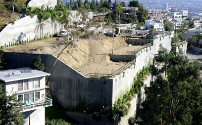 An example of inappropriate development with massive grading and huge retaining walls. Notice how the home on the left is dwarfed by this project.