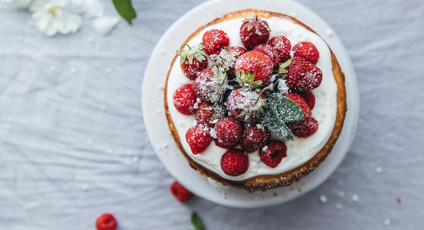 Belegt mit Himbeeren und Erdbeeren ist der Victoria Sponge Cake ein sommerlicher Genuss auf jeder Kaffeetafel.