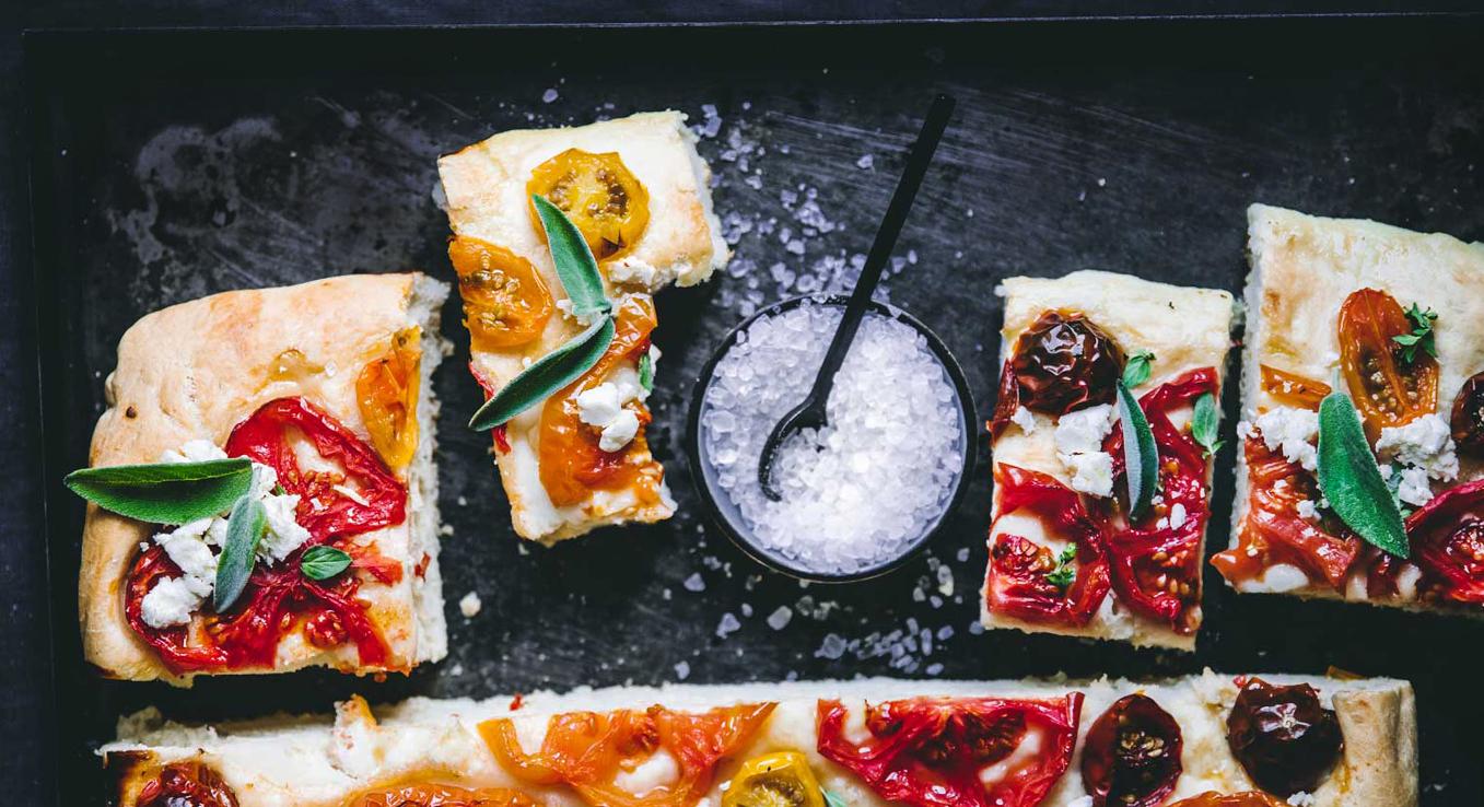 Focaccia mit bunten Tomaten in verschiedenen Größen, Kräuter-Knoblauch-Öl und Schafskäse: Unser Must-have bei jedem Picknick.