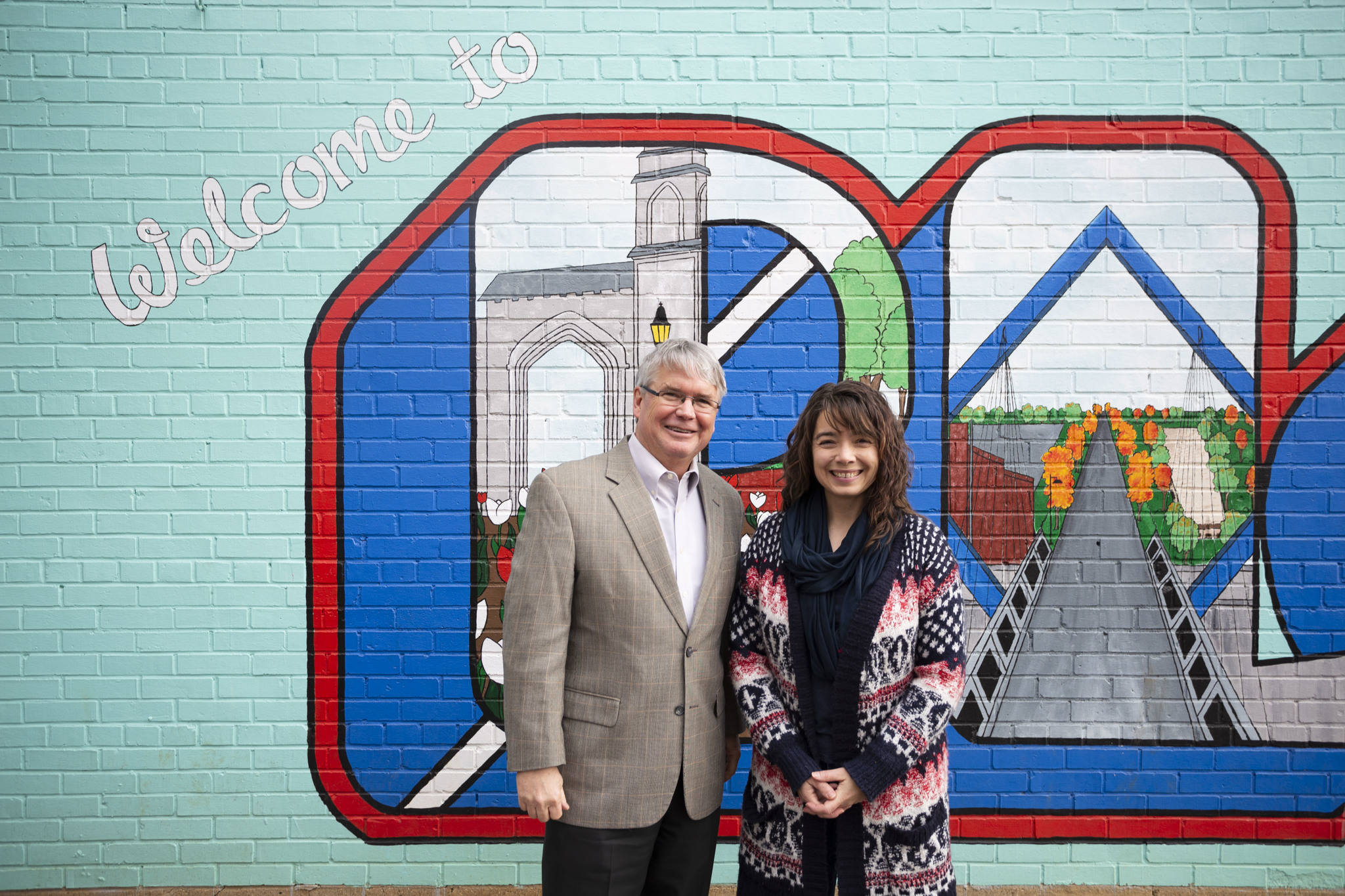 "John with Eva Rohlfing Allen, the artist of the ""Welcome to Bloomington"" mural in People's Park"