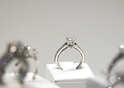 The white-gold solitaire is complete, under glass, and for sale.