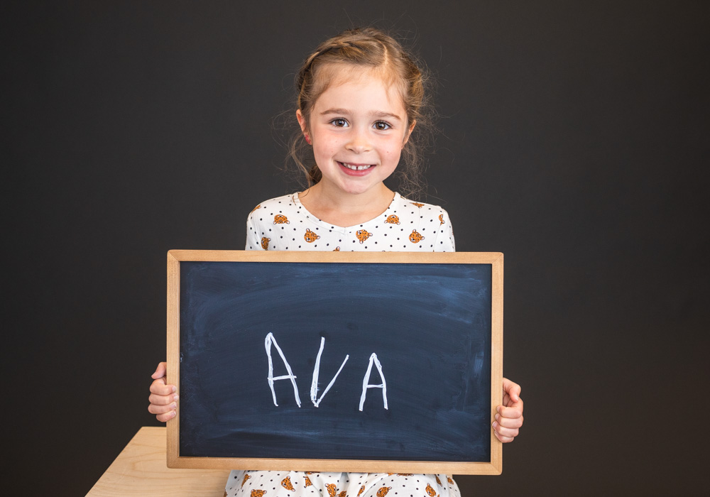 Children write their names on a blackboard as a way of recording their handwriting for the school year.