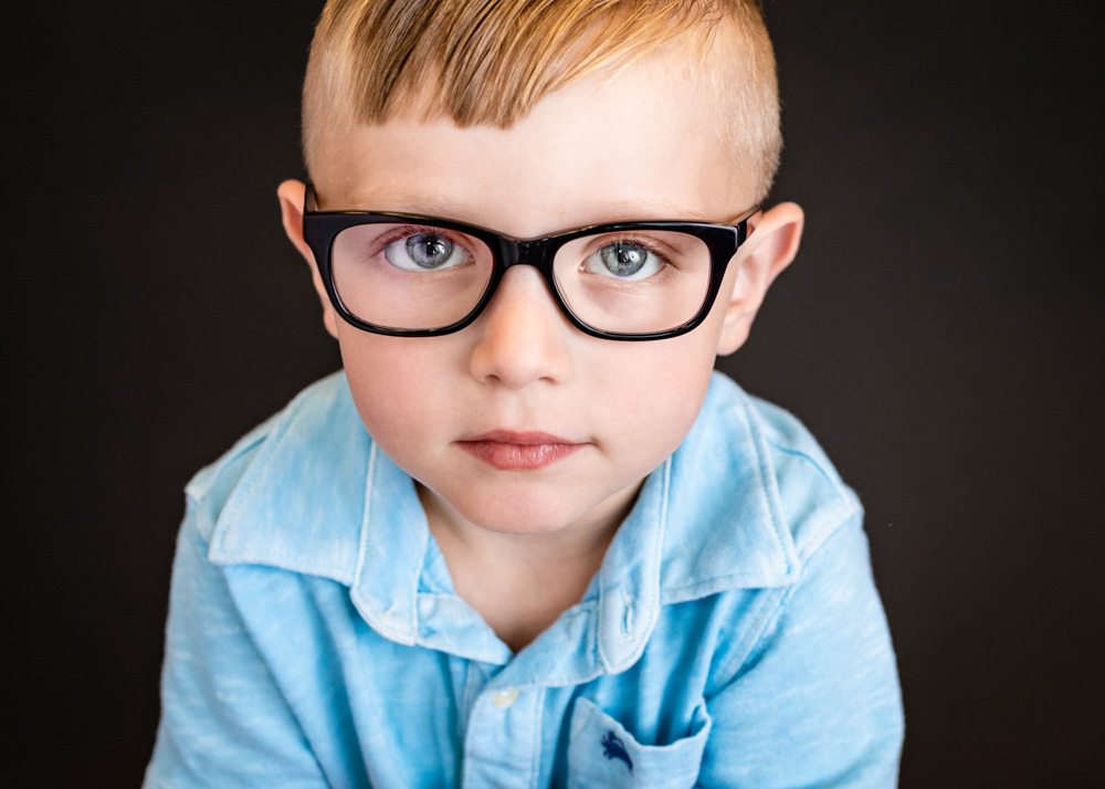 """A media filter is often added to children's glasses which reflects blue or purple in a photo. When possible, I remove it. If I am unable to remove it, I can send it off to a lab for removal. If you want glass glare removed from any pics, just add that picture to the cart and click on """"glass glare removal."""" The cost is $2.50 per image."""