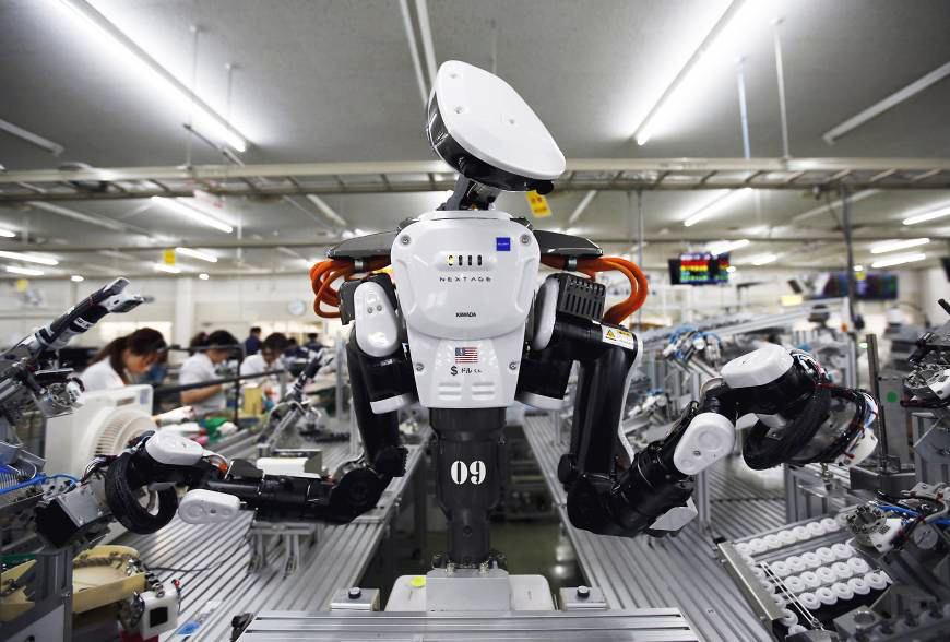 A humanoid robot works with employees on an assembly line at a factory of Glory Ltd.