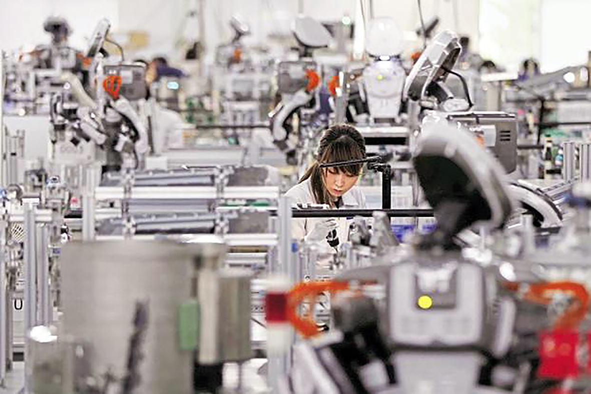 A human worker and humanoid robot working on the same assembly line.