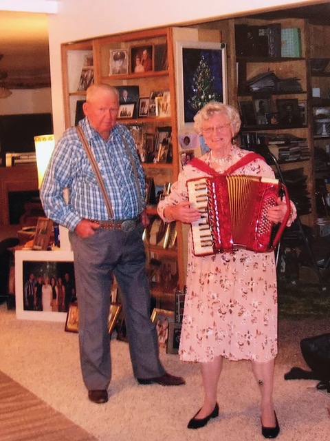 Celia Sandoz Ostrander Barth plays her prized Swiss accordion in her living room while husband Lyle looks on