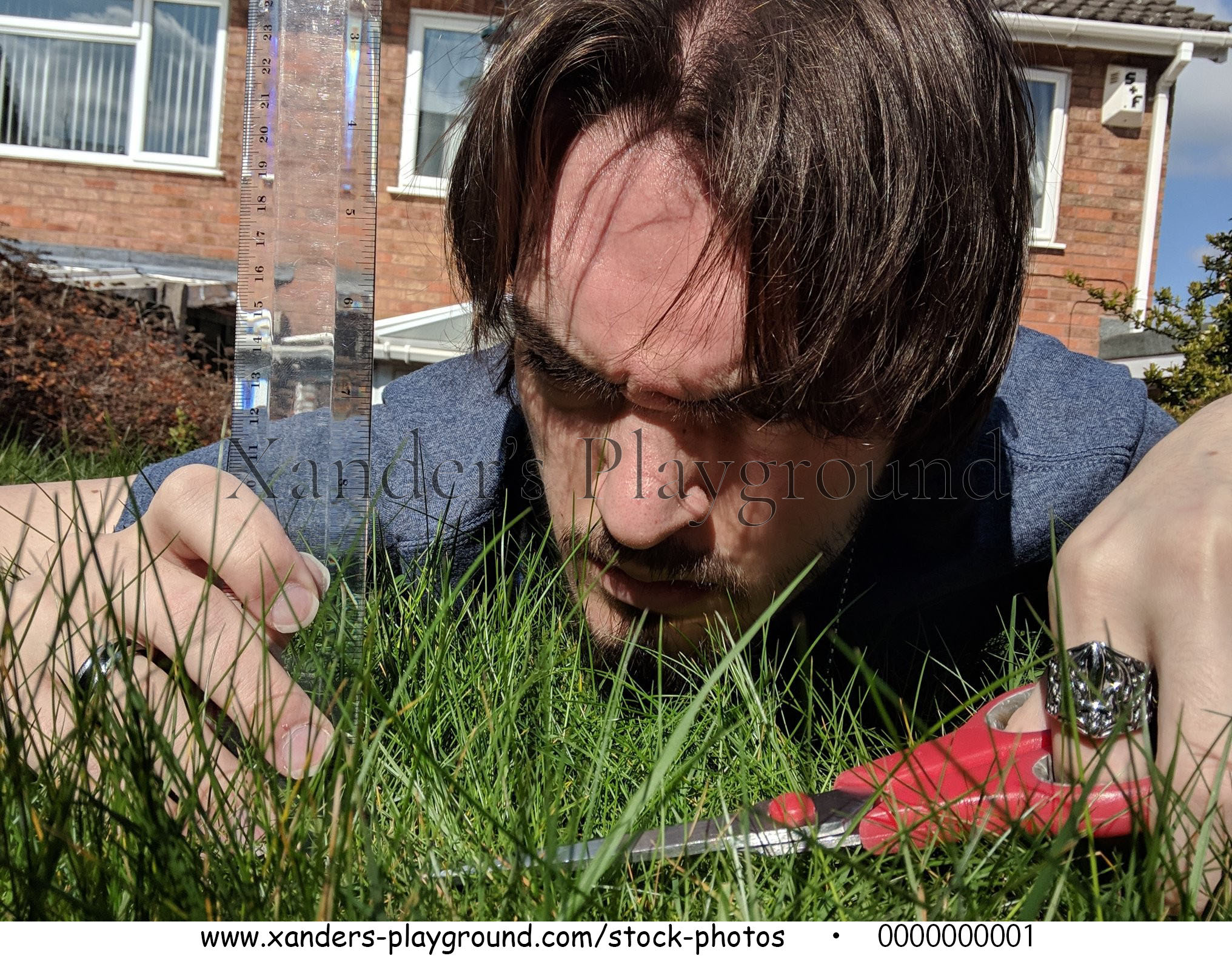 Close-up Of Xander Using Measuring Scale While Cutting Grass With Scissors