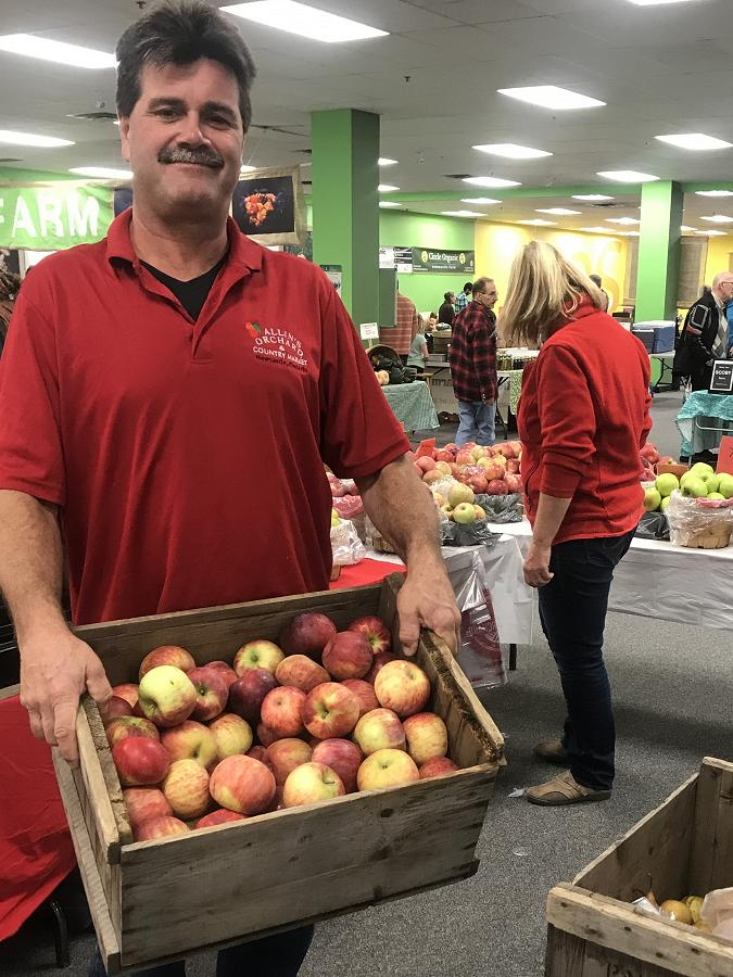 Brian Allin hauls crates of apples from Allin's Orchards to the winter location of the Peterborough Regional Farmers' Market in Peterborough Square. (Photo: Barb Shaw / kawarthaNOW.com)
