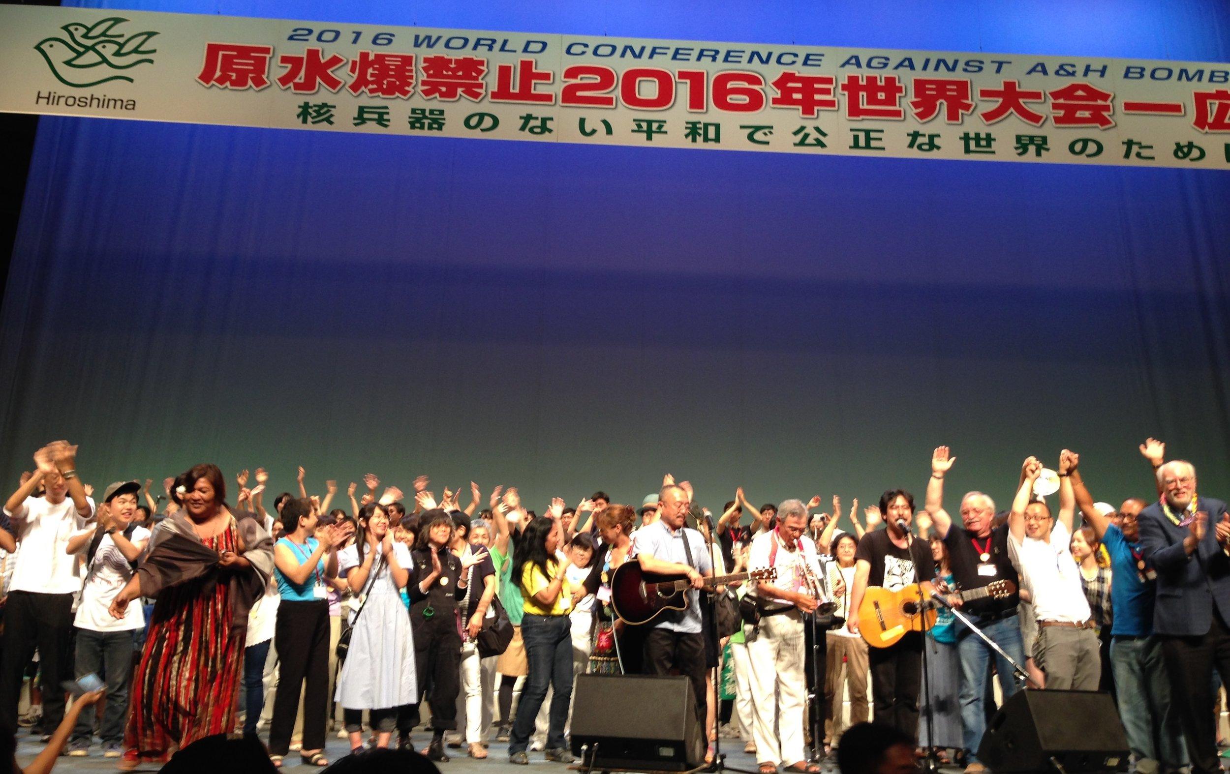 원자폭탄과수소폭탄 반대를 위한 세계 회의 폐막식에서 전 세계에서 온 참가자와 일본 대표자들이 무대에 나와 '우리는 이겨낼 것이다  We Shall Overcome '를 합창하였다. (사진: 팻 앤젤레스)