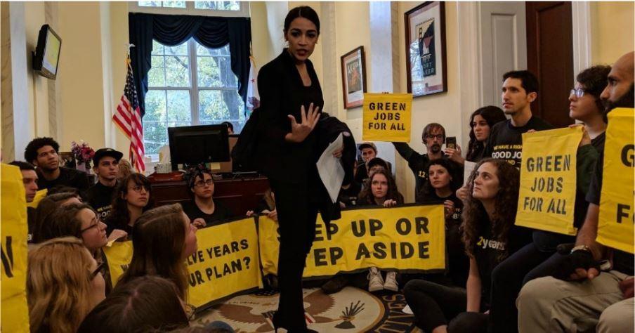 민주당 하원의원인 알렉산드리아 오카시오-코르테스가 기후변화 활동가와 함께 넨시 펠로시 하원의원 사무실 앞을 점거하고 있다. 출처: Common Dreams