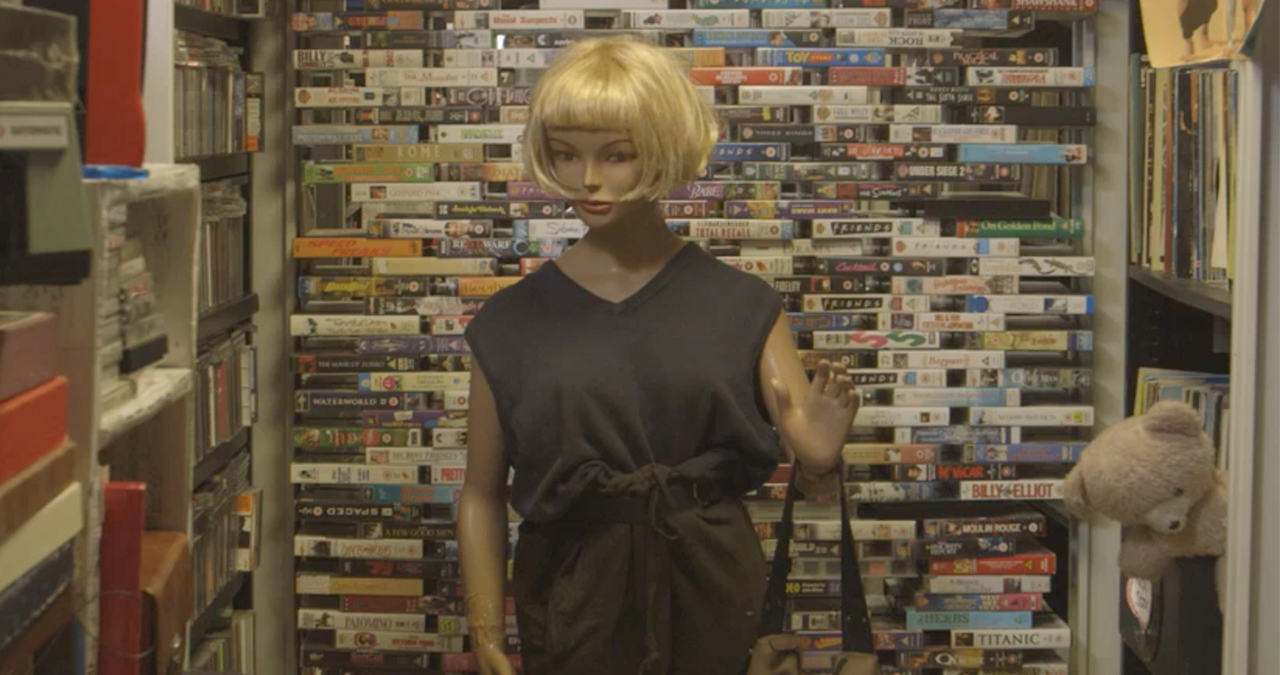 A mannequin of a woman stands in front of a wall made out of VHS tapes. A still from short film The Gruntles.