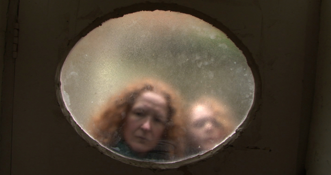 A mother and child peer through a frosted round window. A still from short film, Aargh!