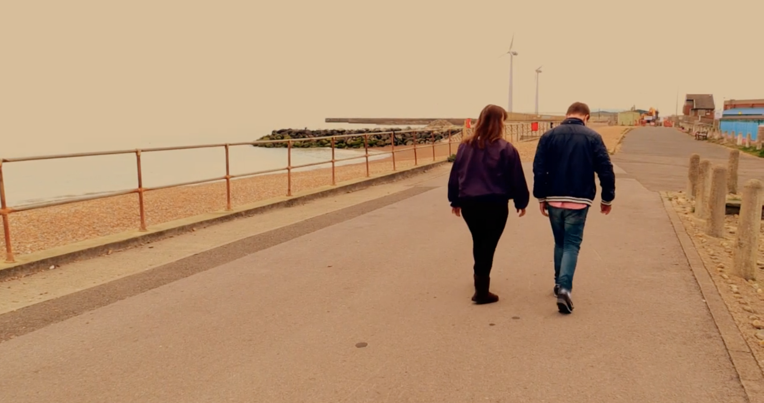 A young couple walking along a beach promenade. A still from short film, One in a Million.