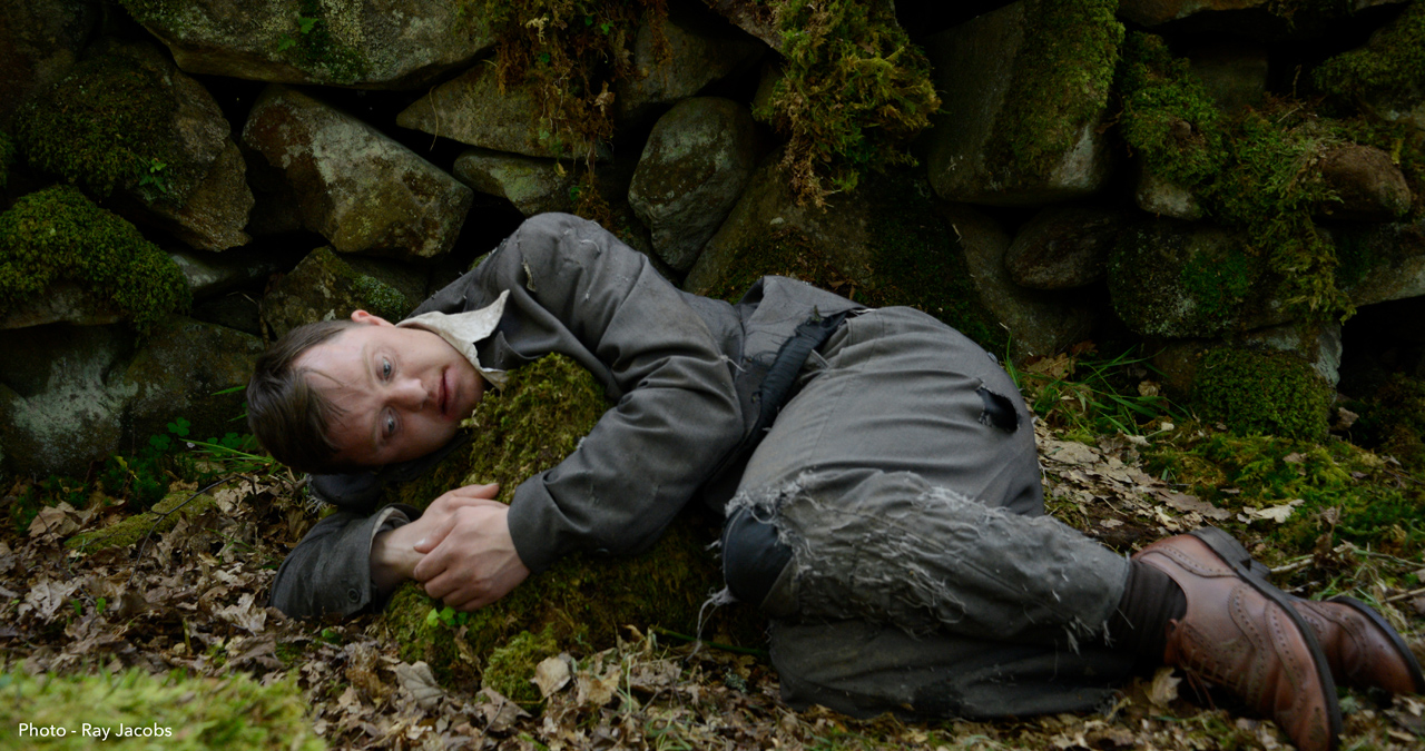 A man in a suit lies in a forest hugging a rock. A still from short film A Safe Place to Rest.
