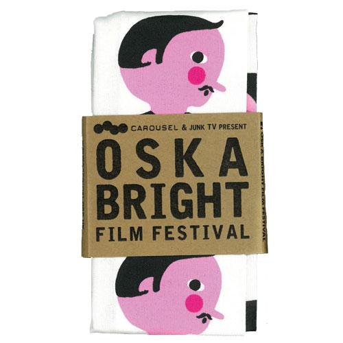 A folded Oska Bright Film Festival tea towel showing design by Billy Mather.