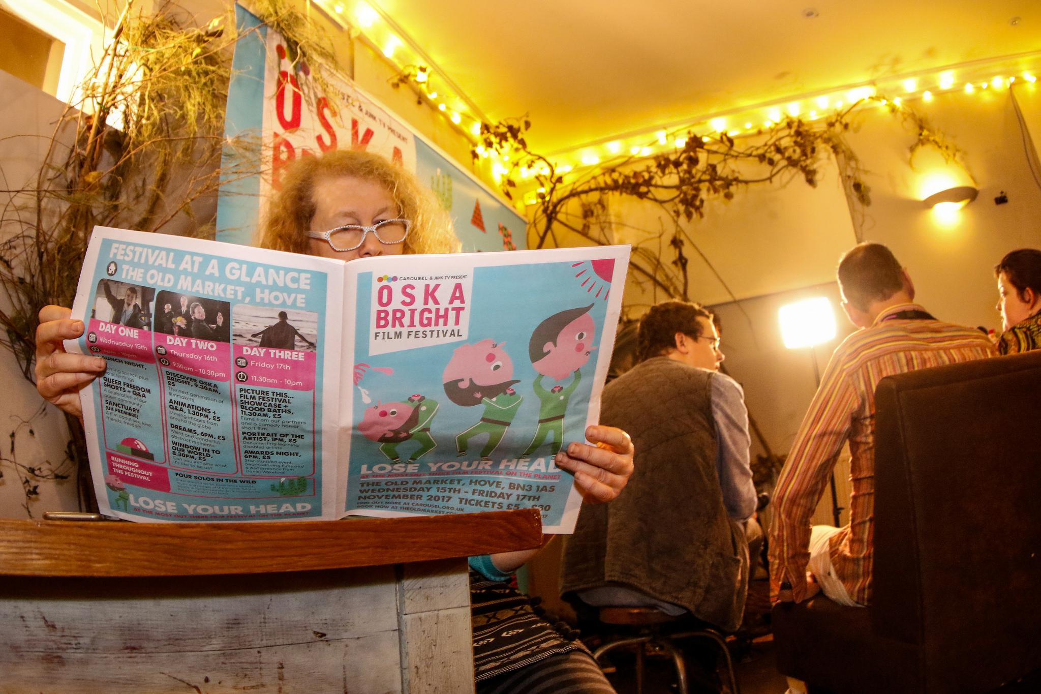 A woman reads the Oska Bright Film Festival programme in the bar at The Old Market.