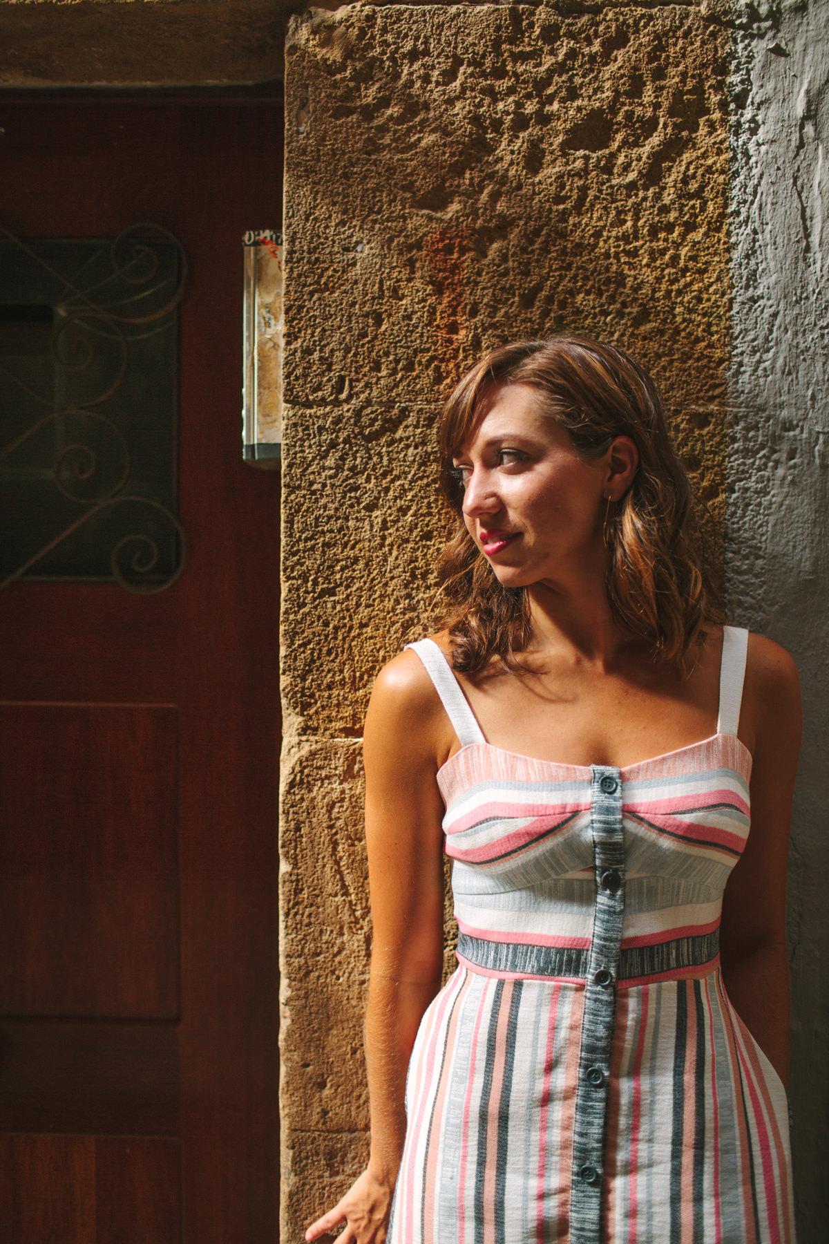 retrato chica apoyada en la pared en la calle mirando al sol