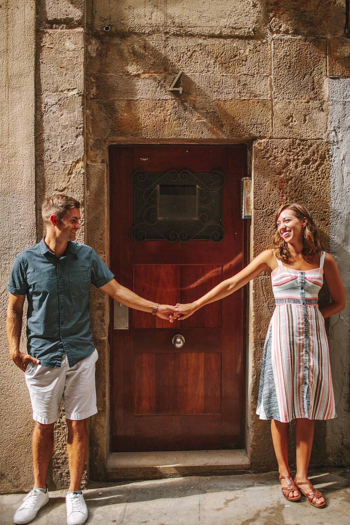 Pareja de pie cogidas de la mano frente a una puerta en la calle