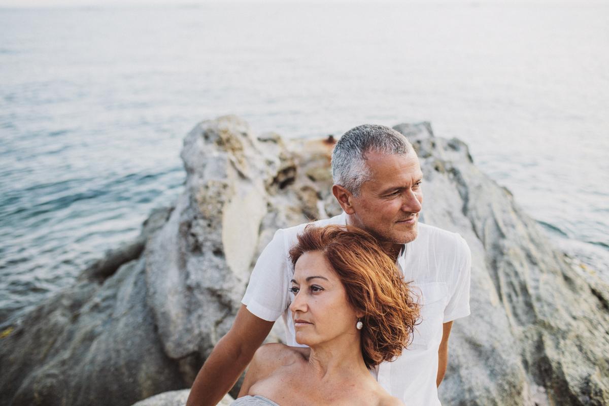 pareja tumbados en una roca en la playa
