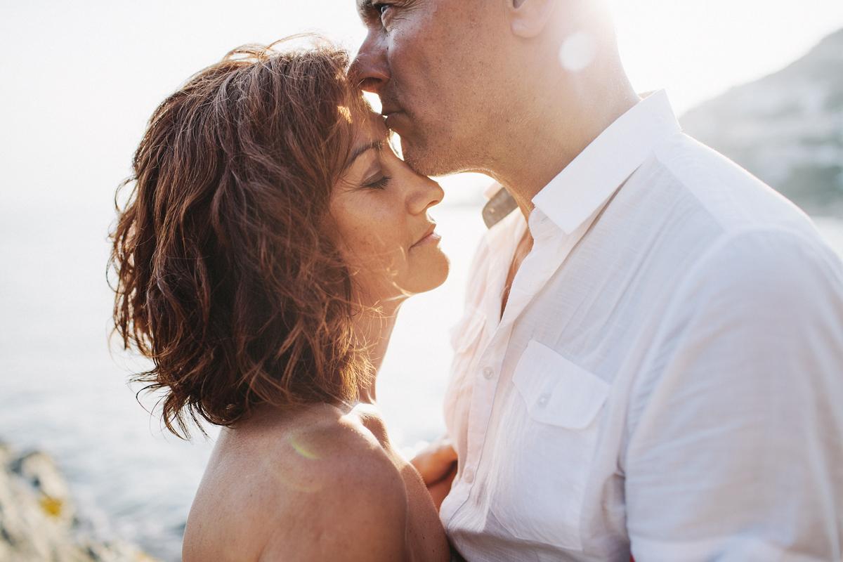 pareja, hombre besa en la frente a la mujer delante de la playa