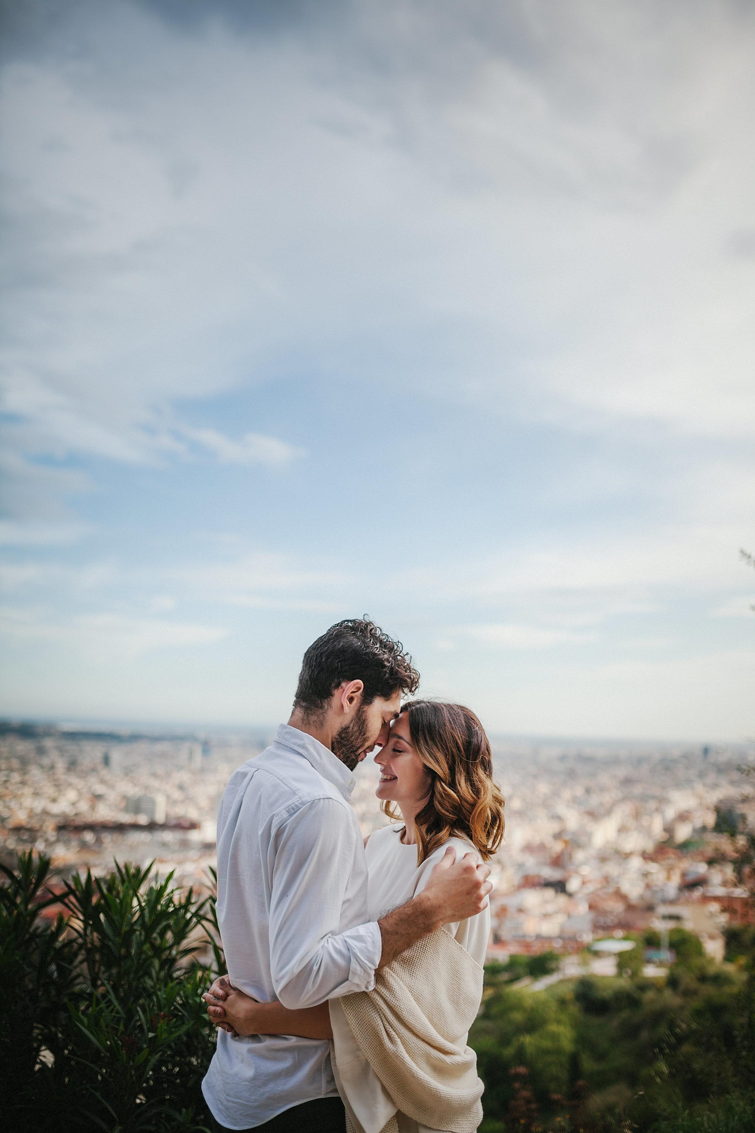 Pareja abrazándose con Barcelona de fondo.
