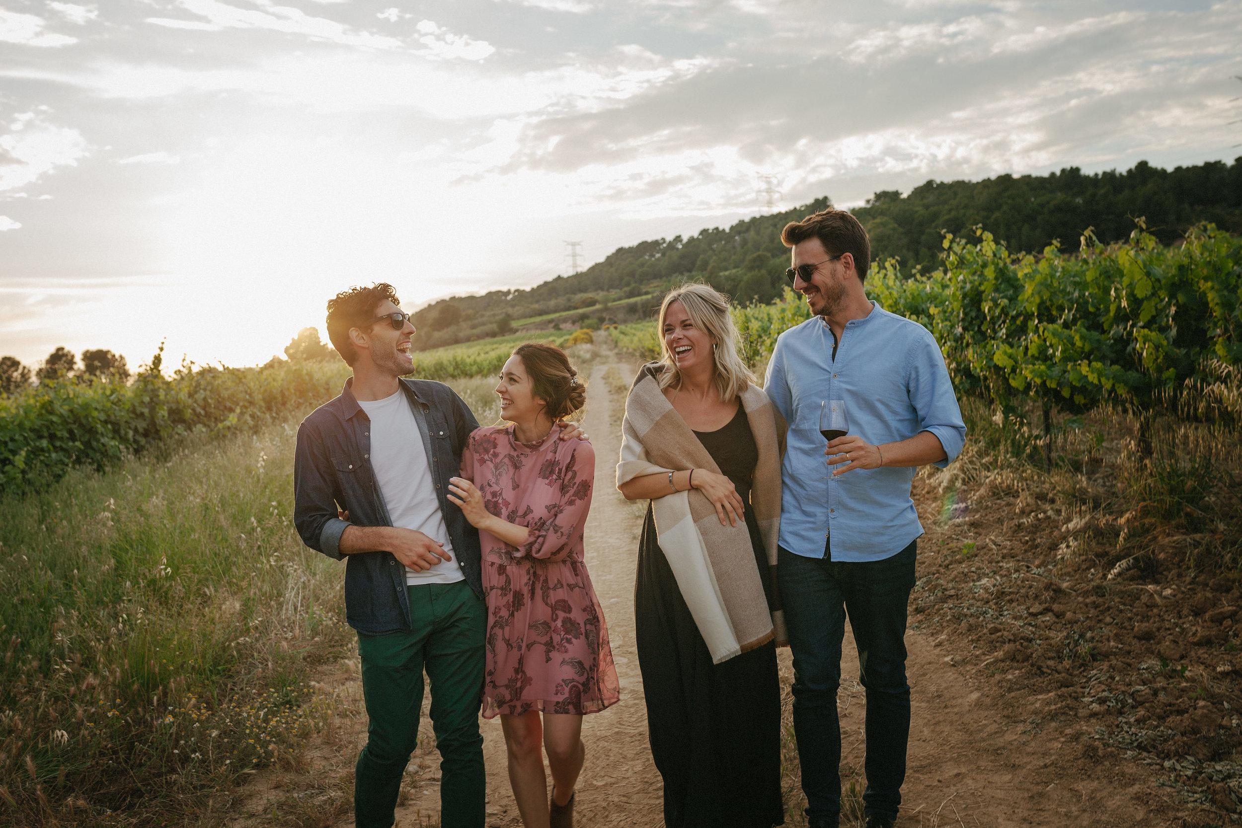 Grupo de amigos riendo caminando por viñas del Penedés