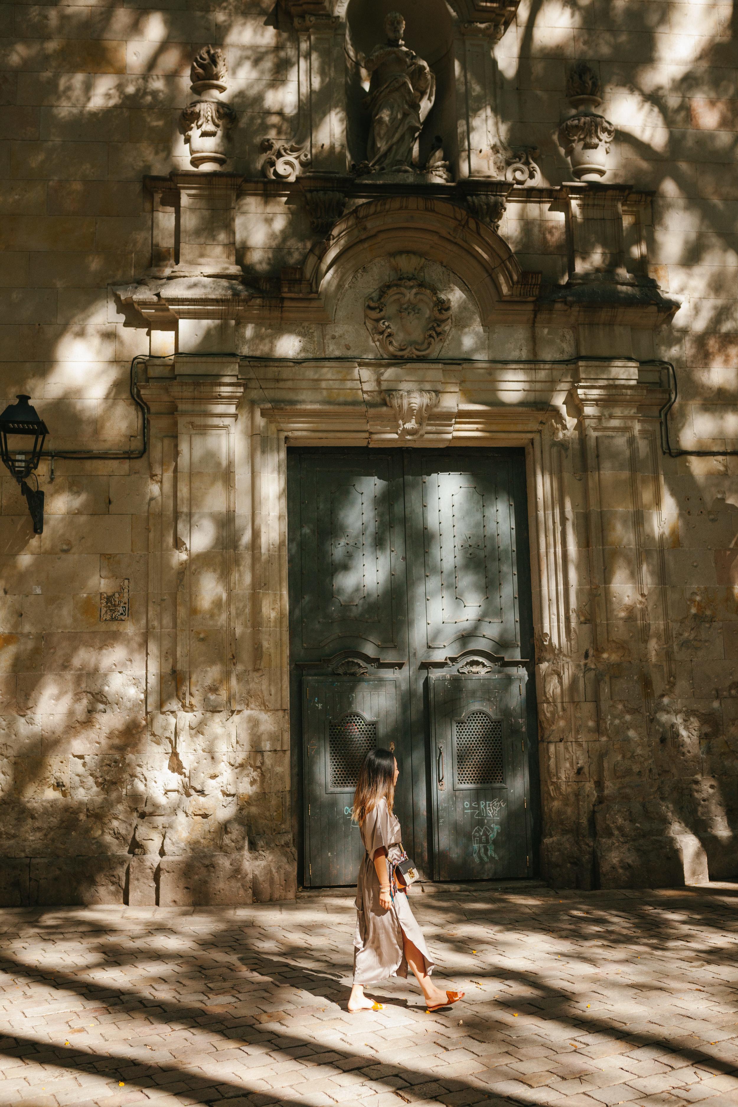 Chica caminando bajo las sombras de la plaza Felip Neri de Barcelona