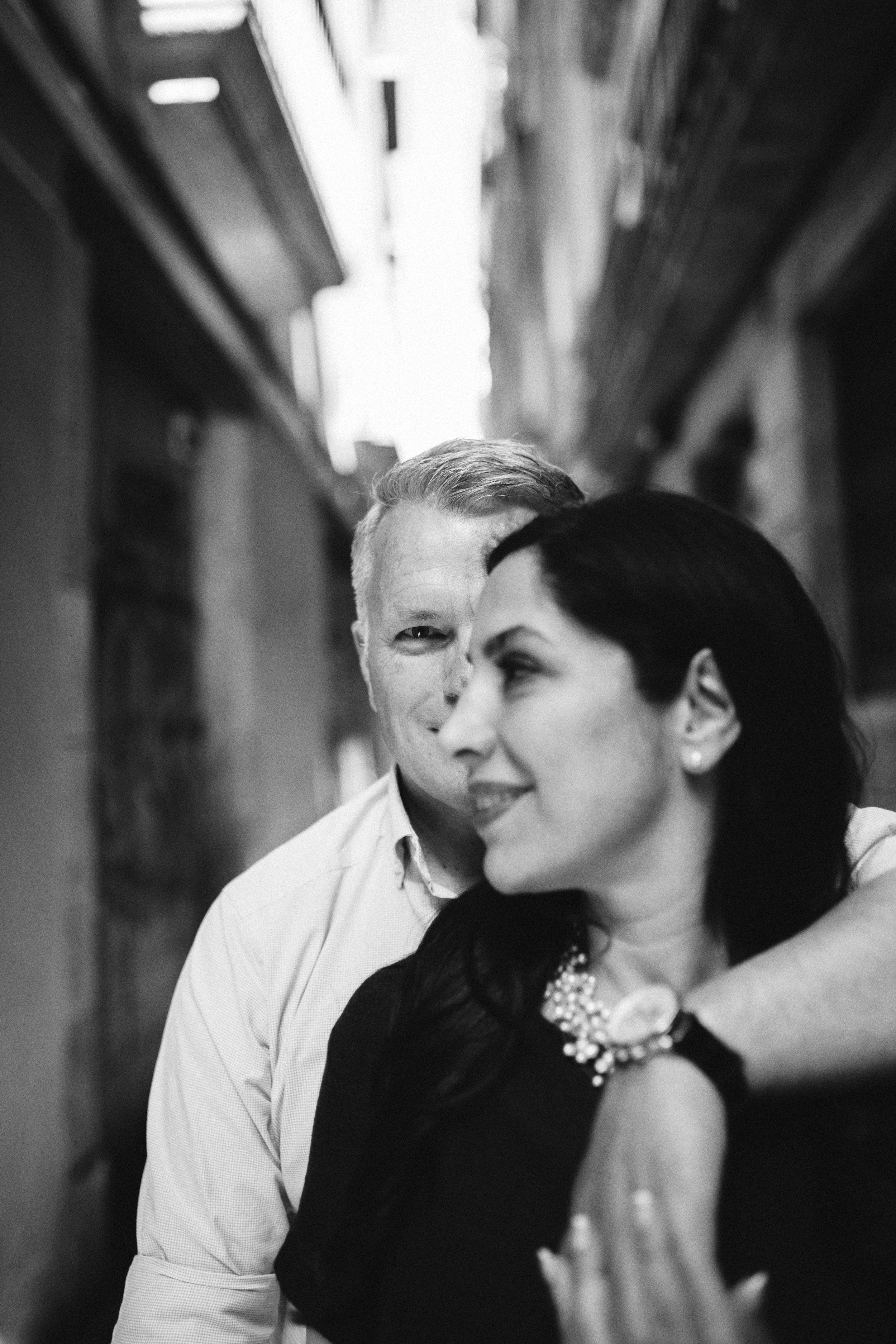hombre mirando fíjamente abrazando a mujer que mira a un lado.
