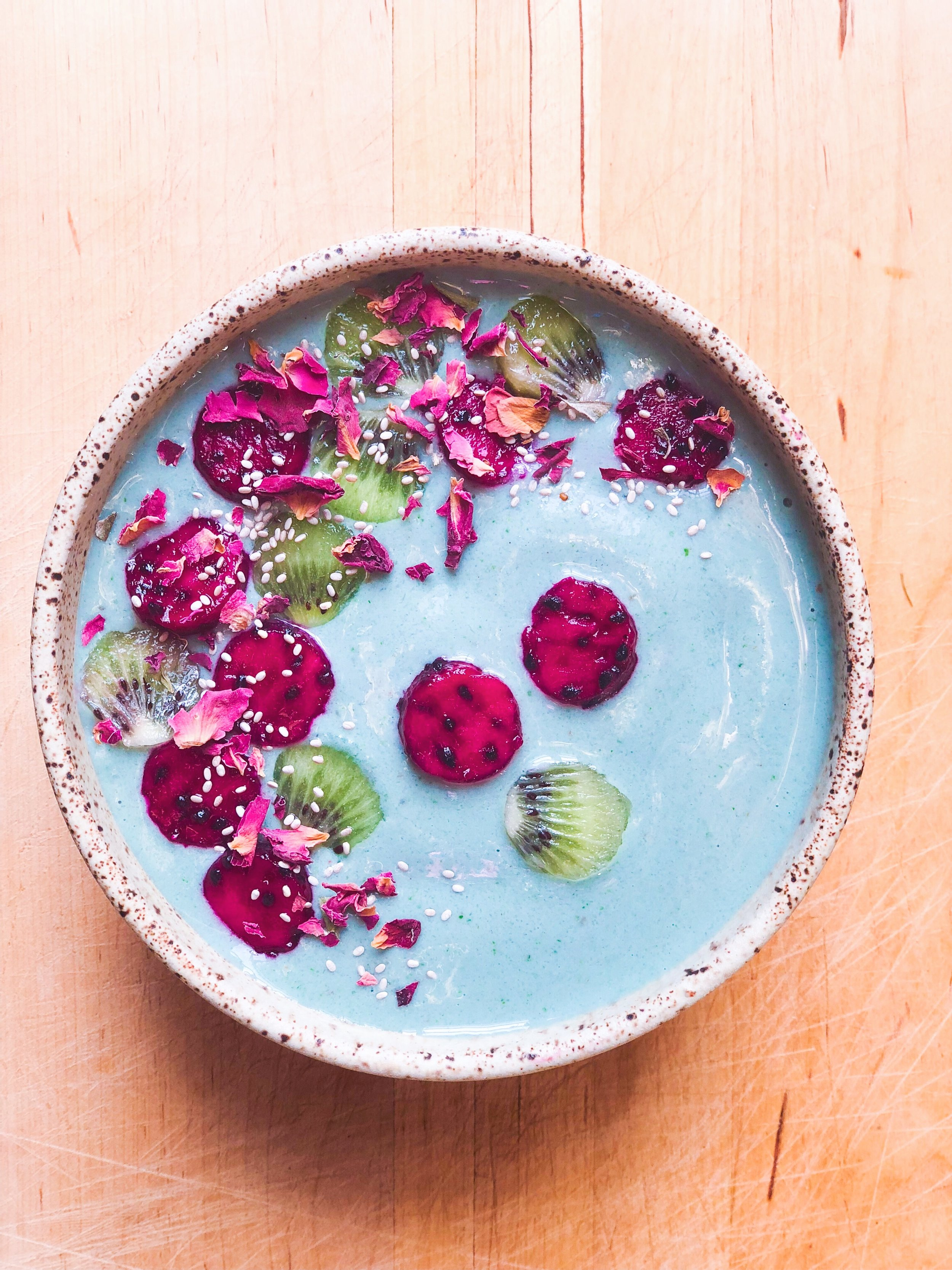Blue smoothie bowl with kiwi, strawberry and rose petals