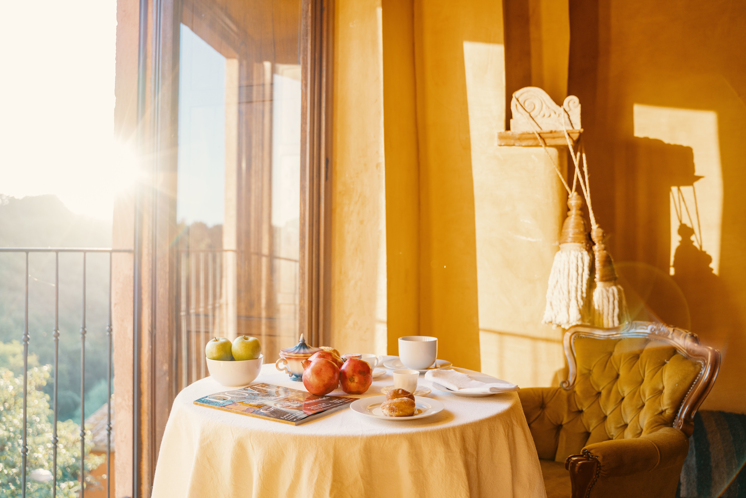 Sunny view of a breakfast table with fruits and croissants.