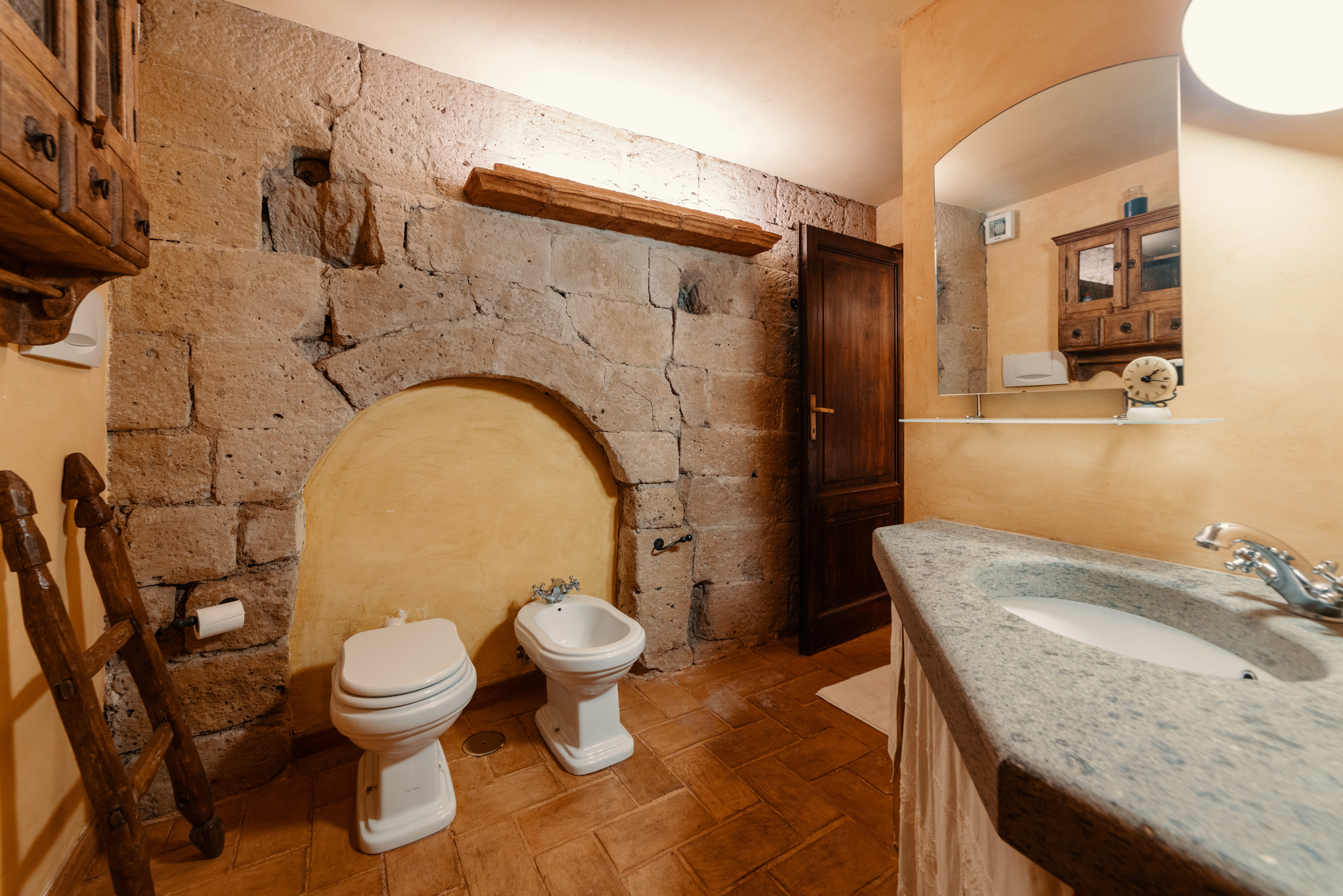 Rustic bathroom with toilet, bidet and shower.
