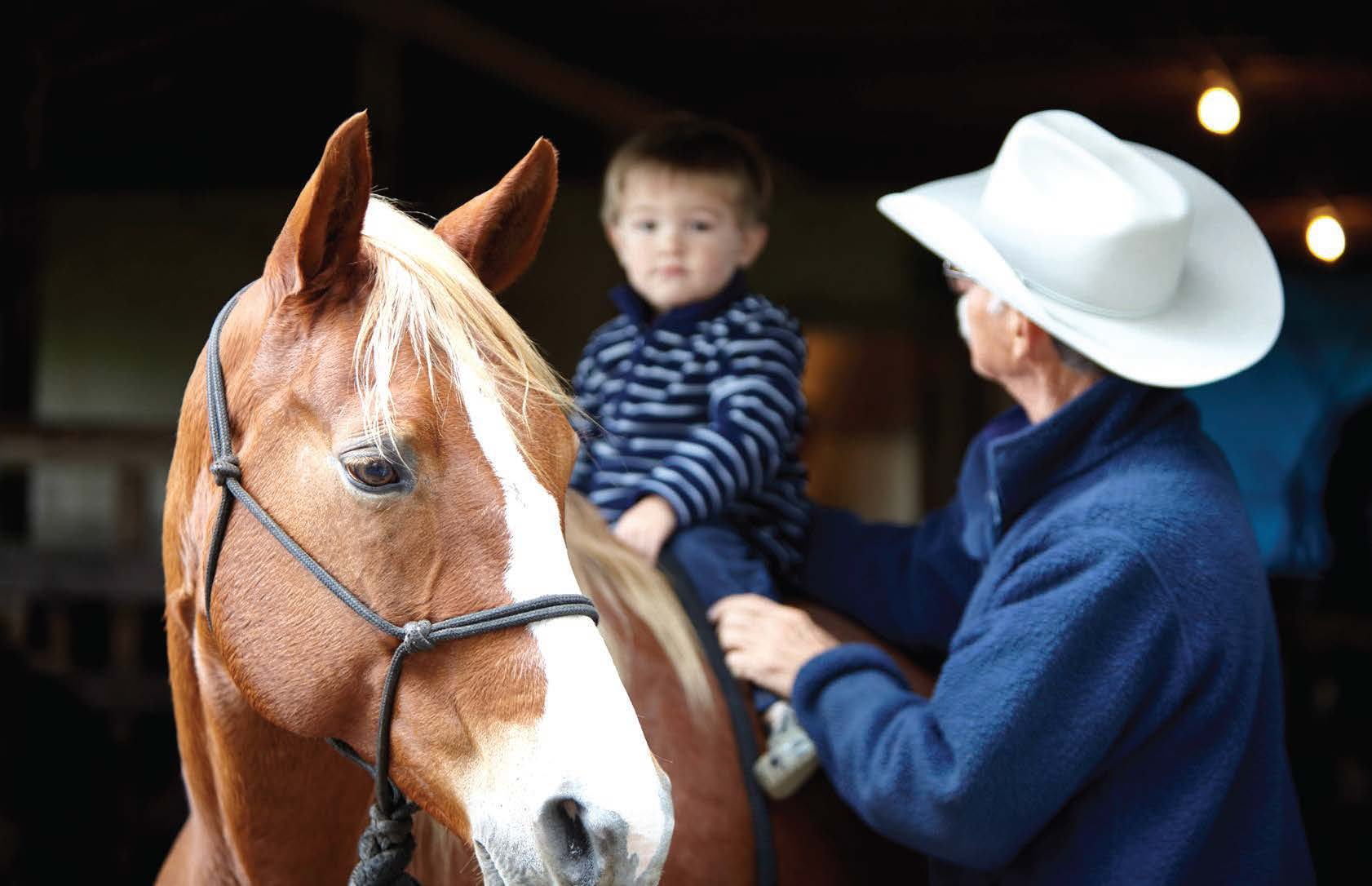 Ralph Pelaez with his grandson McKinley on their 1,375-acre ranch in Okeechobee County. Photo by Randy Batista