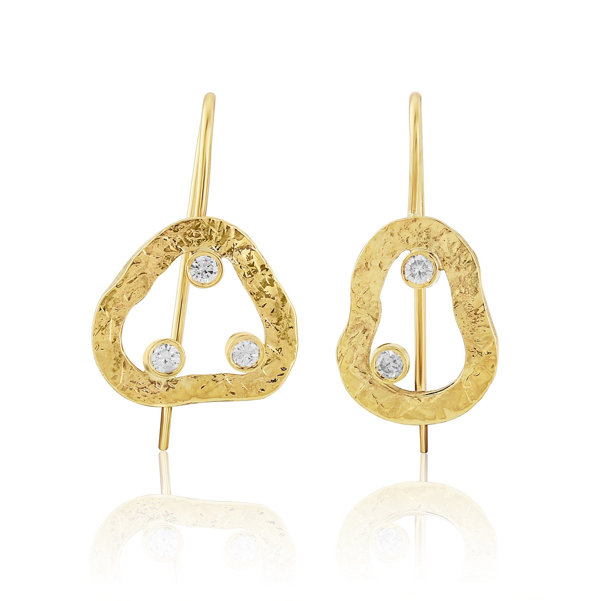 A mismatched pair of gold earrings with diamonds in a textured finish