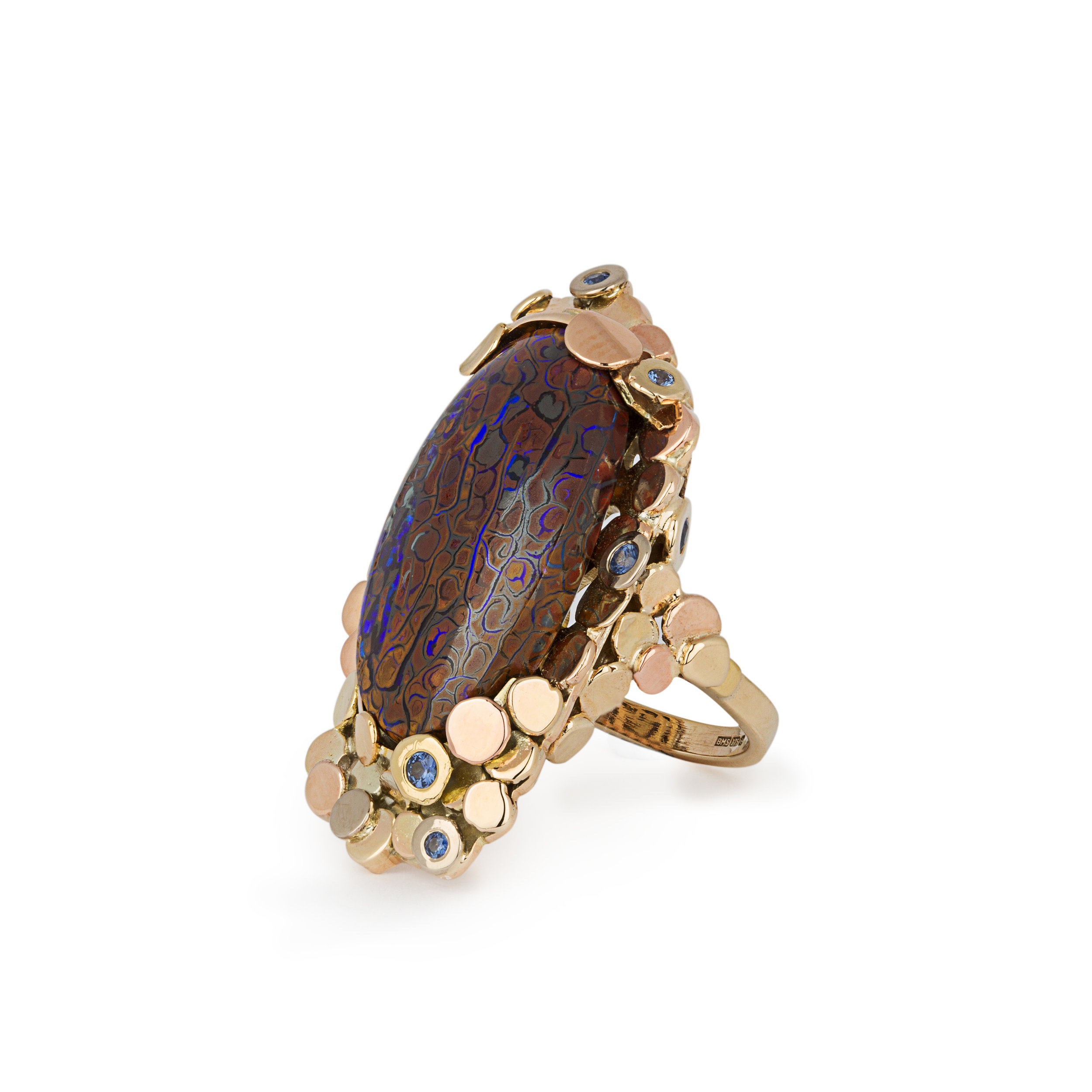 Recovered ship wrecked coins was the idea behind this ring a large koroite boulder opal with ceylon blue sapphires set around the design in mixed colours of gold 9ct and 18ct