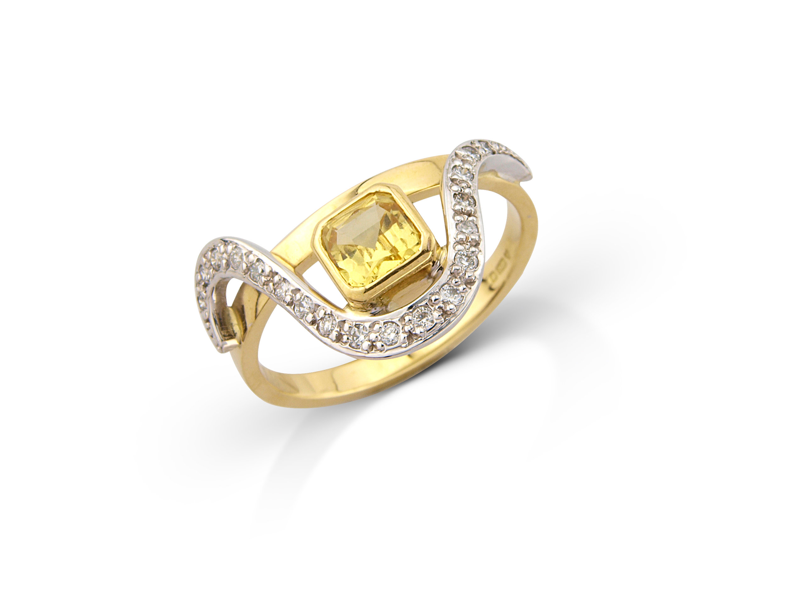 Yellow sapphire dress ring mounted in 18ct yellow gold and set with diamonds in white gold.