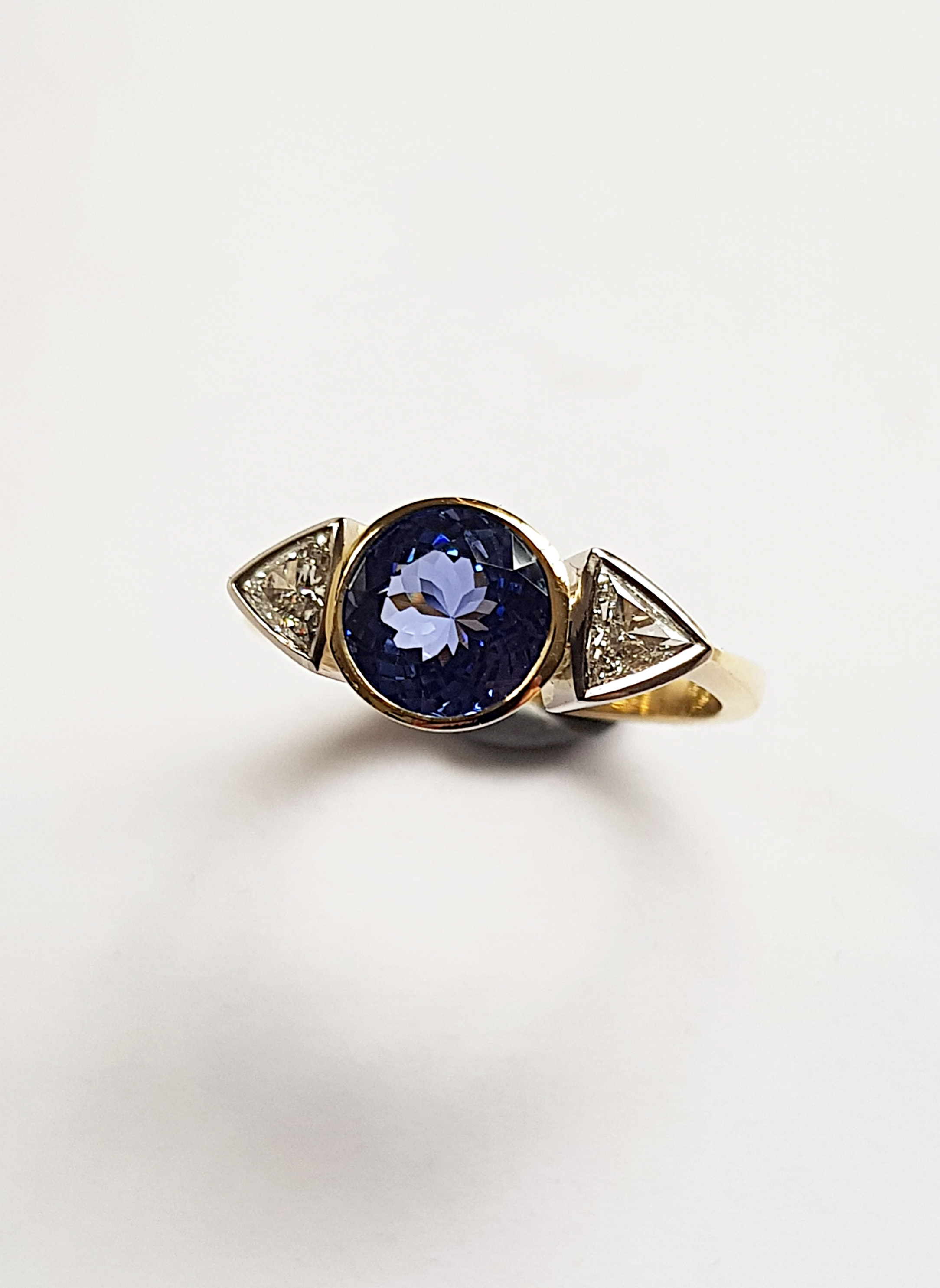 Precision cut Top quality Sapphire flanked by two trilliant cut Diamonds classically mounted in 18ct gold all hand made out of fresh metal ie no cast components by QVJ.