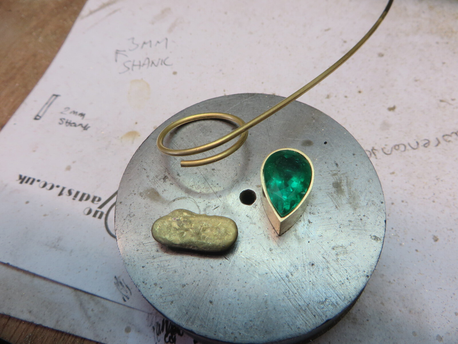 Start of the Commission process, showing the setting part of the ring and an ingot of Gold ,all this gold is from the clients own old Jewellery and is being remodeled into a new Emerald/Diamond ring.